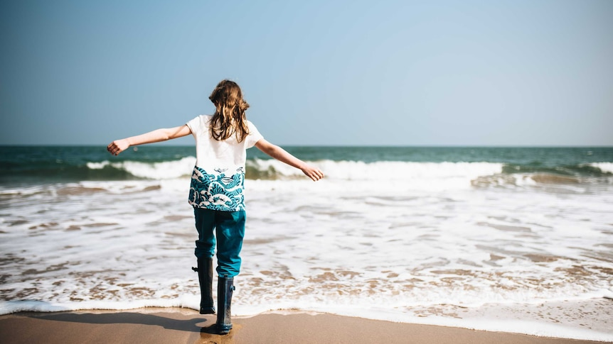 A woman facing the ocean holding her arms out with no-one else around for a story about taking mum vacations alone.