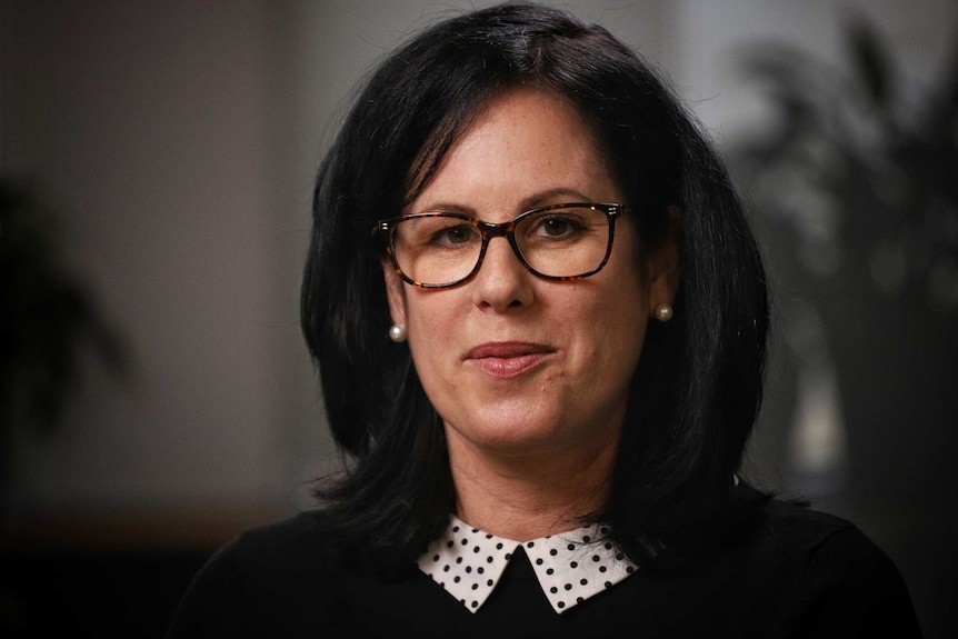 Dr Caitlin Curtis wears a black top and glasses.