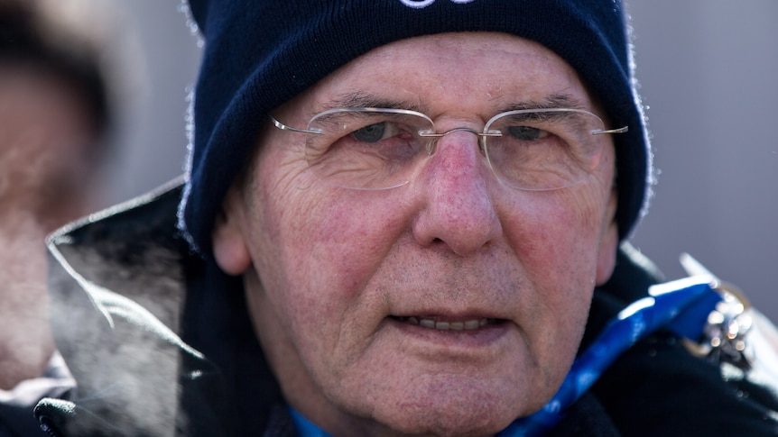 Jacques Rogges wearing glasses and a beanie with the Olympic rings on it
