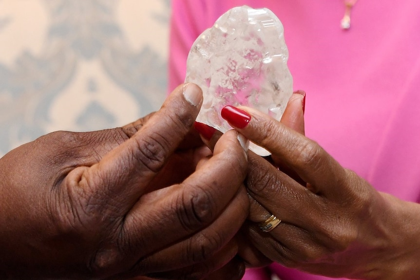A man and a woman's hand hold a large diamond