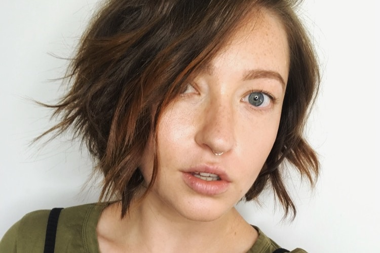 A close-shot of a woman with short wavy hair and dark green top, and nose ring, with neutral expression.