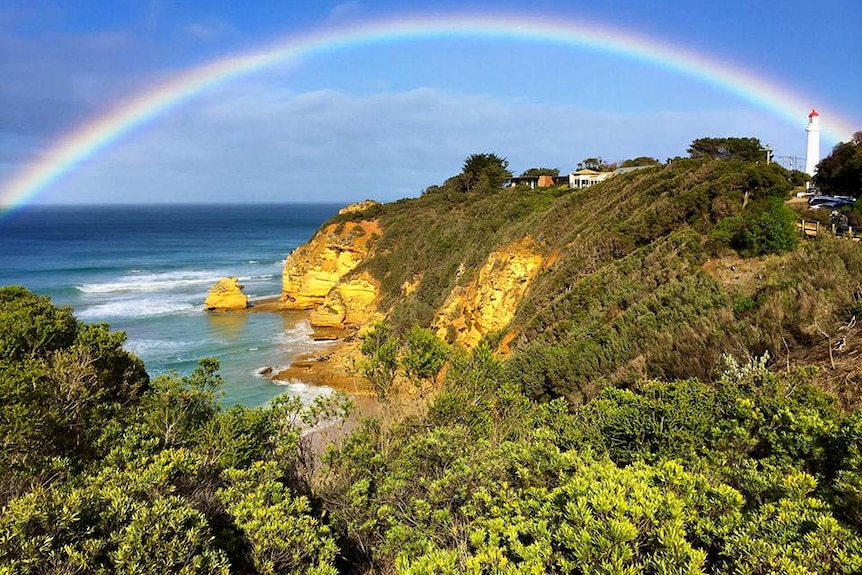 A rainbow stretches from the beach over the orange cliffs of aireys inlet to the famous local white with red roof lighthouse