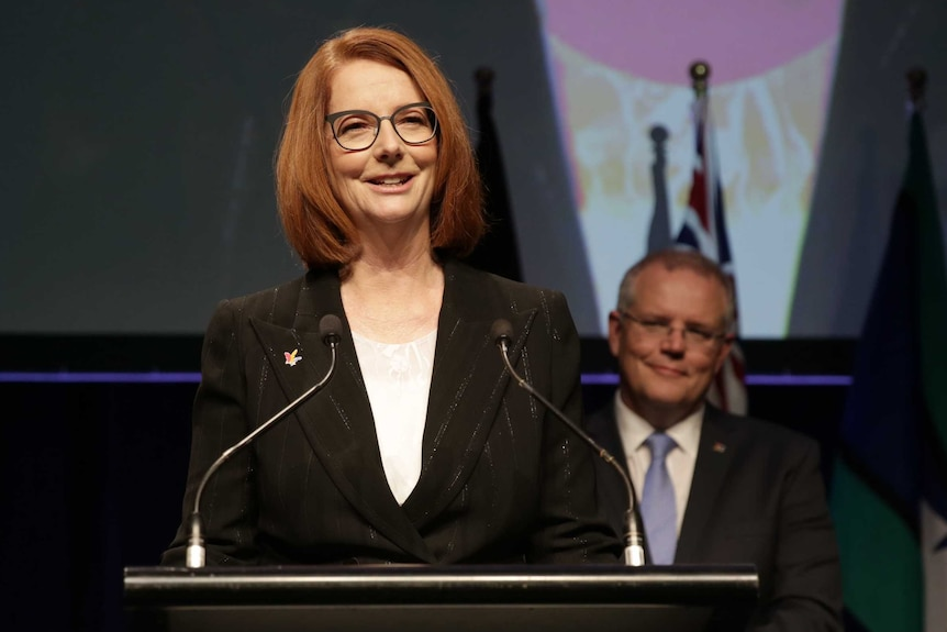 Julia Gillard stands at a podium smiling out at the audience, while Scott Morrison looks on from behind, also smiling.