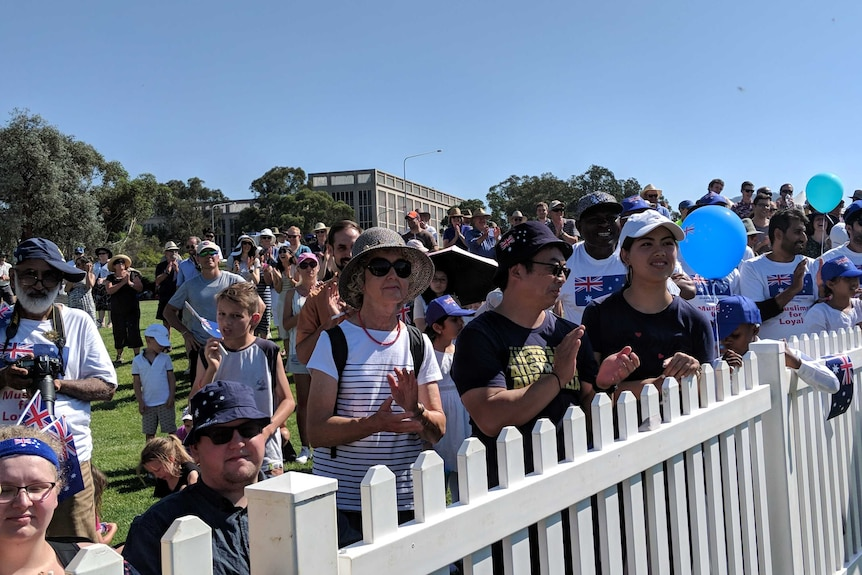 People waving Australia flags in Canberra to watch Australian citizenship ceremonies.