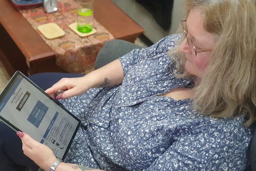 a woman sitting on a chair looking at a centrelink website on her ipad