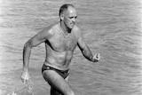 Black and white photo of man in swimwear running through ocean