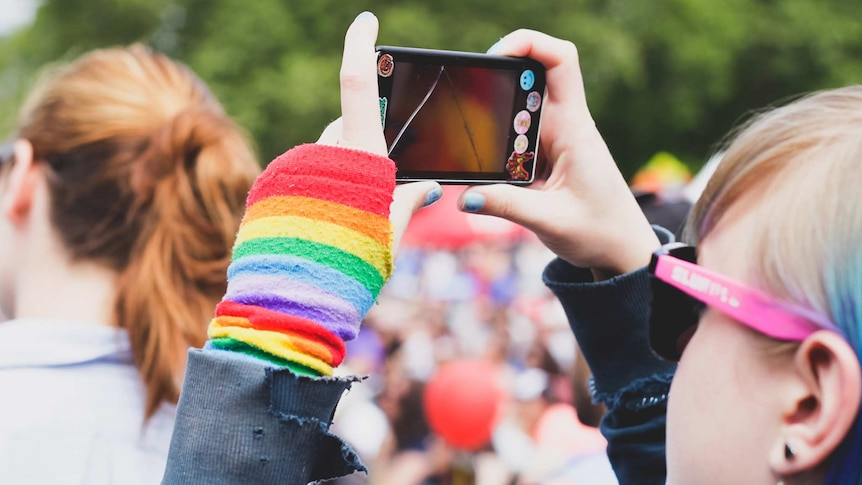 A young woman at an LGBT pride festival takes a photo.