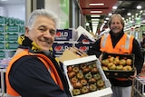 Harry Kapiris (left) and Frank Mileto hold boxes of tomatoes at the Melbourne Markets.