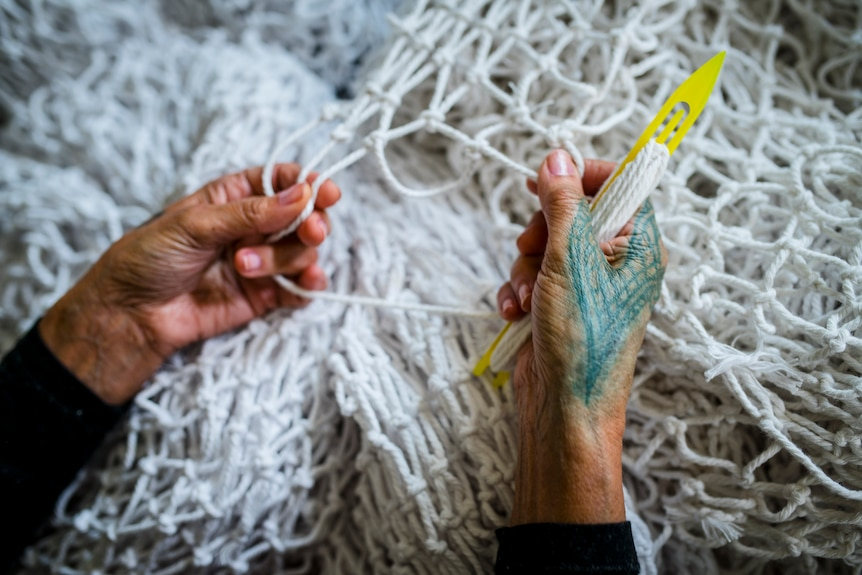 Close up photo of two hands working on weaving a white net.