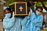 Two women wearing PPE carry a coffin with a crucifix painted on the end