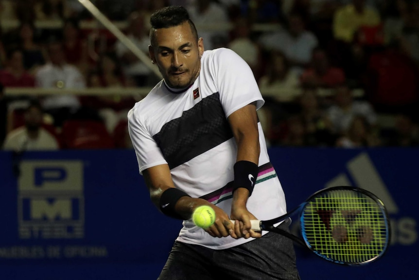 Nick Kyrgios looks down as he hits a double-fisted backhand with his tennis racquet.