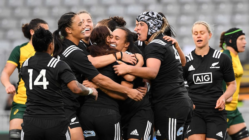 Women's rugby union team celebrate by hugging teammate after scoring a try