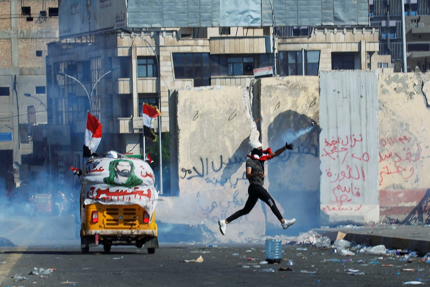 A protester is captured mid air as he leaps up and throws a tear gas canister back at police. Backdrop of run-down buildings