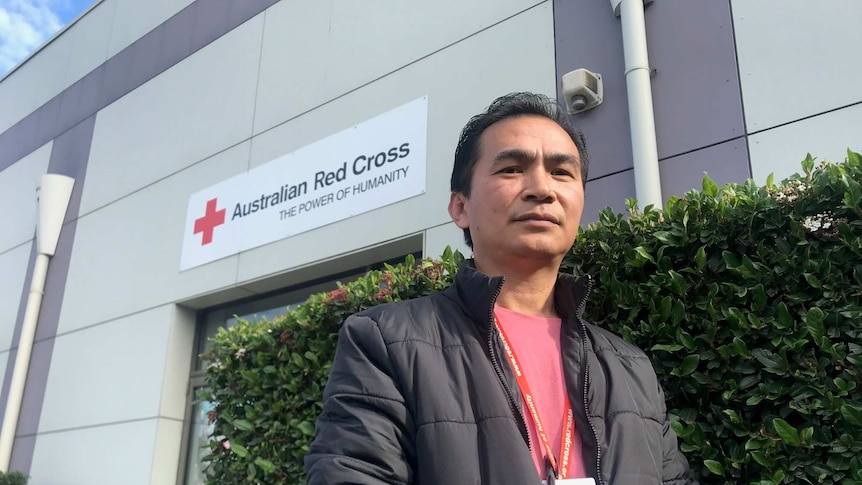 A middle-aged Myanmarese man wearing a puffy jacket and standing in front of an Australian Red Cross building.