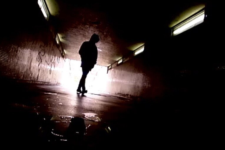 Young person silhouetted in underpass generic image.