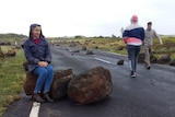 a woman sits on a large boulder which is lying across the road.