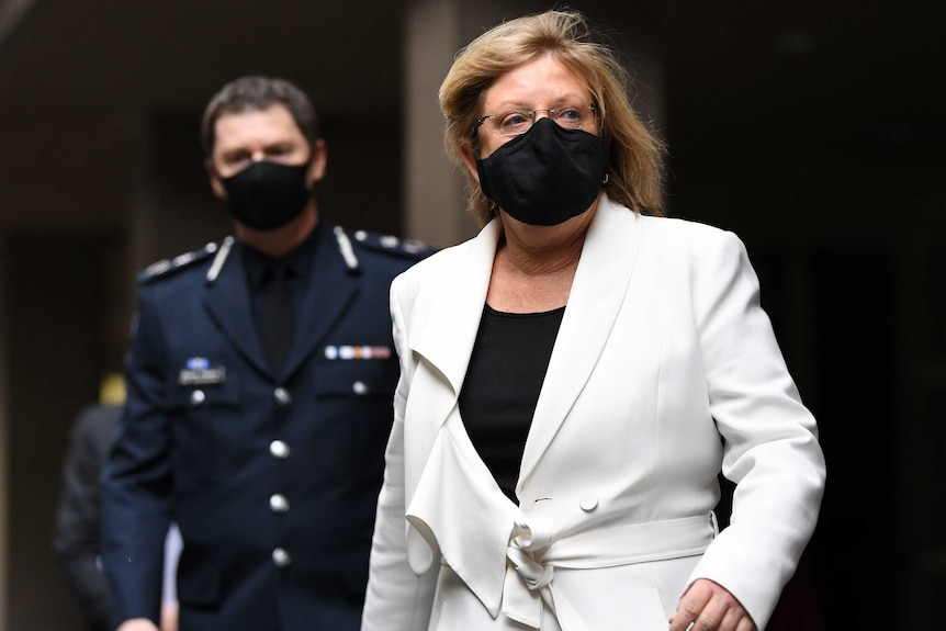 A middle-aged woman wearing a face mask and a while suit walks ahead of masked police officer.