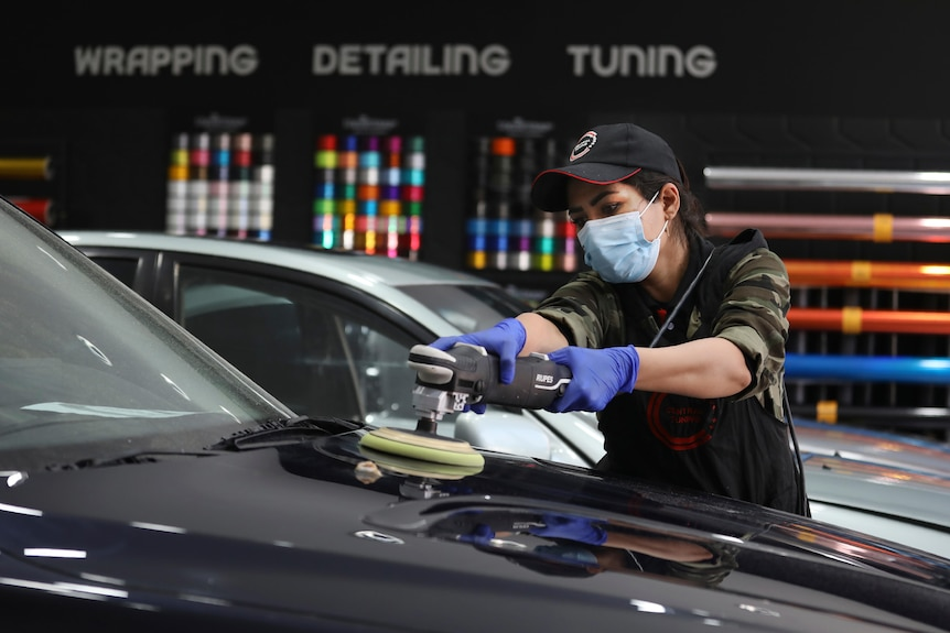 A woman wearing a baseball cap and a blue face mask uses a handheld machine to polish the bonnet of a black car