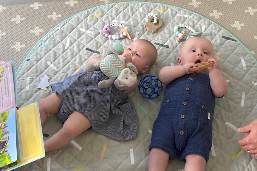 Two newborn babies on the floor surrounded by toys.