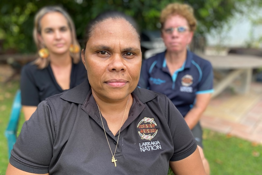 Portrait of a woman Lulu Coombes sitting with her Larrakia Nation colleagues in Darwin
