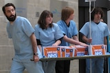 In front of a sandstone building, four people carry a stretcher with four orange boxes that read 'save our NHS'