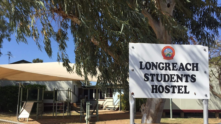 The Longreach Students Hostel sign in front of a collection of buildings.