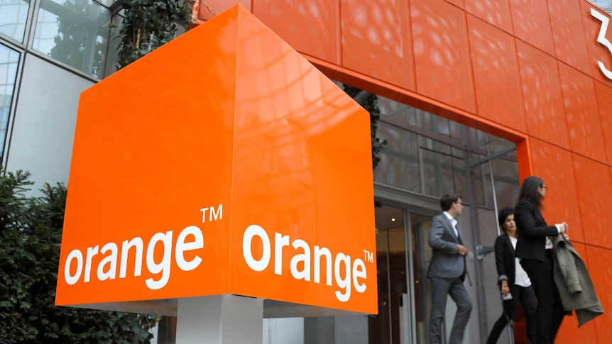 A large square Orange telecom sign is seen in the foreground as three people in corporate attire walk out of sliding glass doors