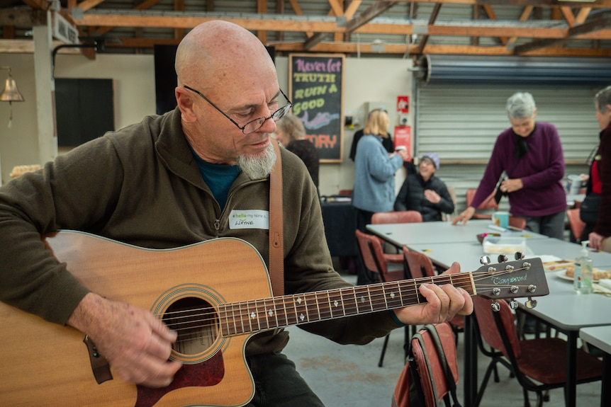 A man sits on a table edge playing guitar in a shed where people are meeting