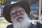 An Indigenous man with a white beard, wearing an Akubra-style hat.