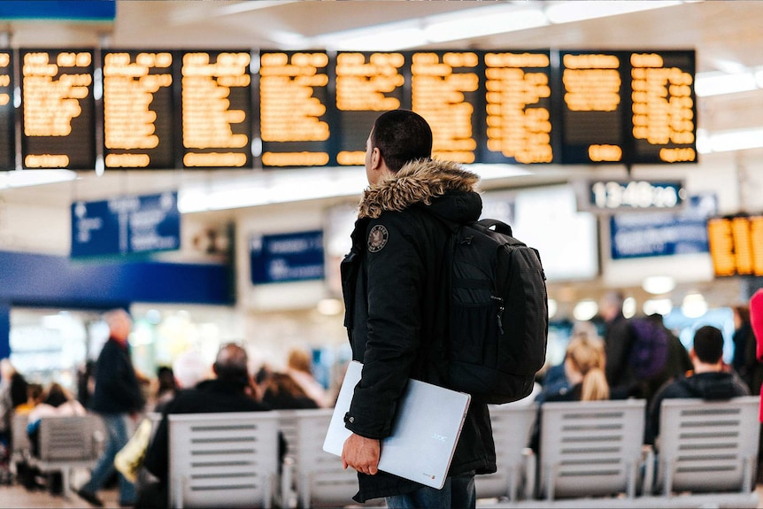 Man wearing a backpack and standing in an airport looking at the departures sign