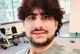 Man in grey top smiles at camera in this selfie.