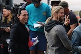 Tom Hiddleston and Chris Hemsworth smile at onlookers on filem set in Brisbane's CBD.