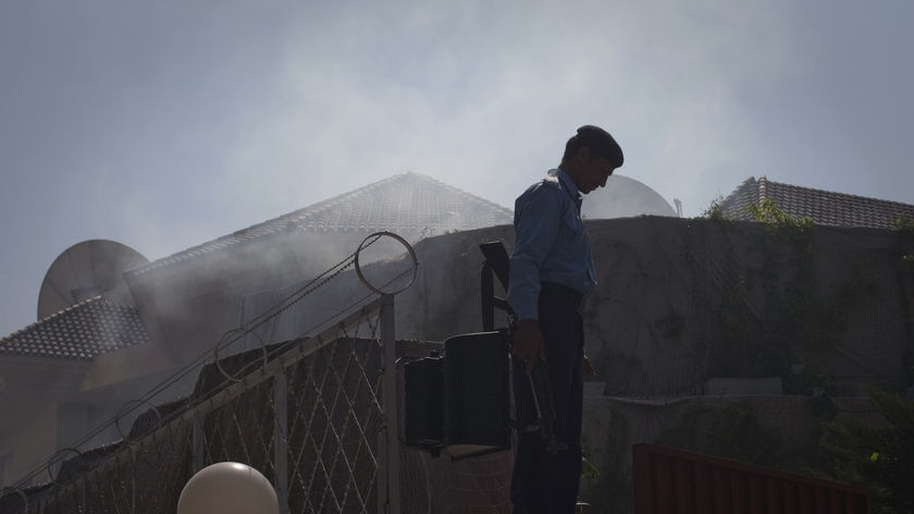 Policeman stands in aftermath of World Food Program suicide attack