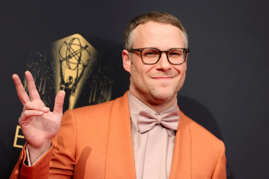 Seth Rogen gives the peace sign to the camera wearing an orange jacket and glasses