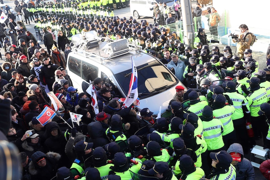 A crowd of protestors and another crowd of police surround a white van.