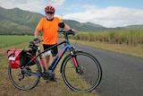 Cyclist with white beard standing behind a bicycle with sugar cane fields in the background