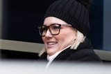 A blonde-haired woman wearing glasses and a beanie.