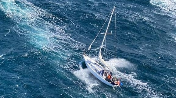 Aerial view of a yacht in choppy sea.