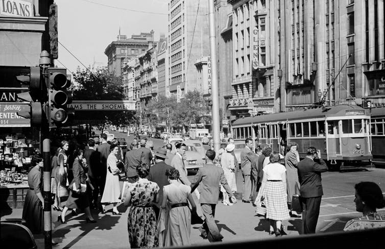 Men in suits and women in dresses walk along Collins Street in a black and white image
