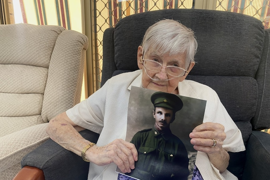An elderly woman with grey hair looks at the camera. She is holding a picture of a soldier.