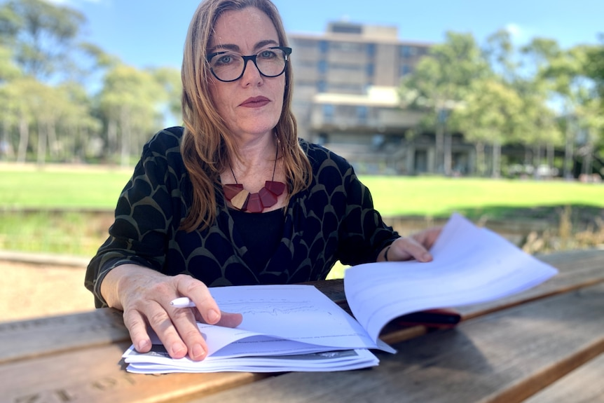 a woman with documents in a park