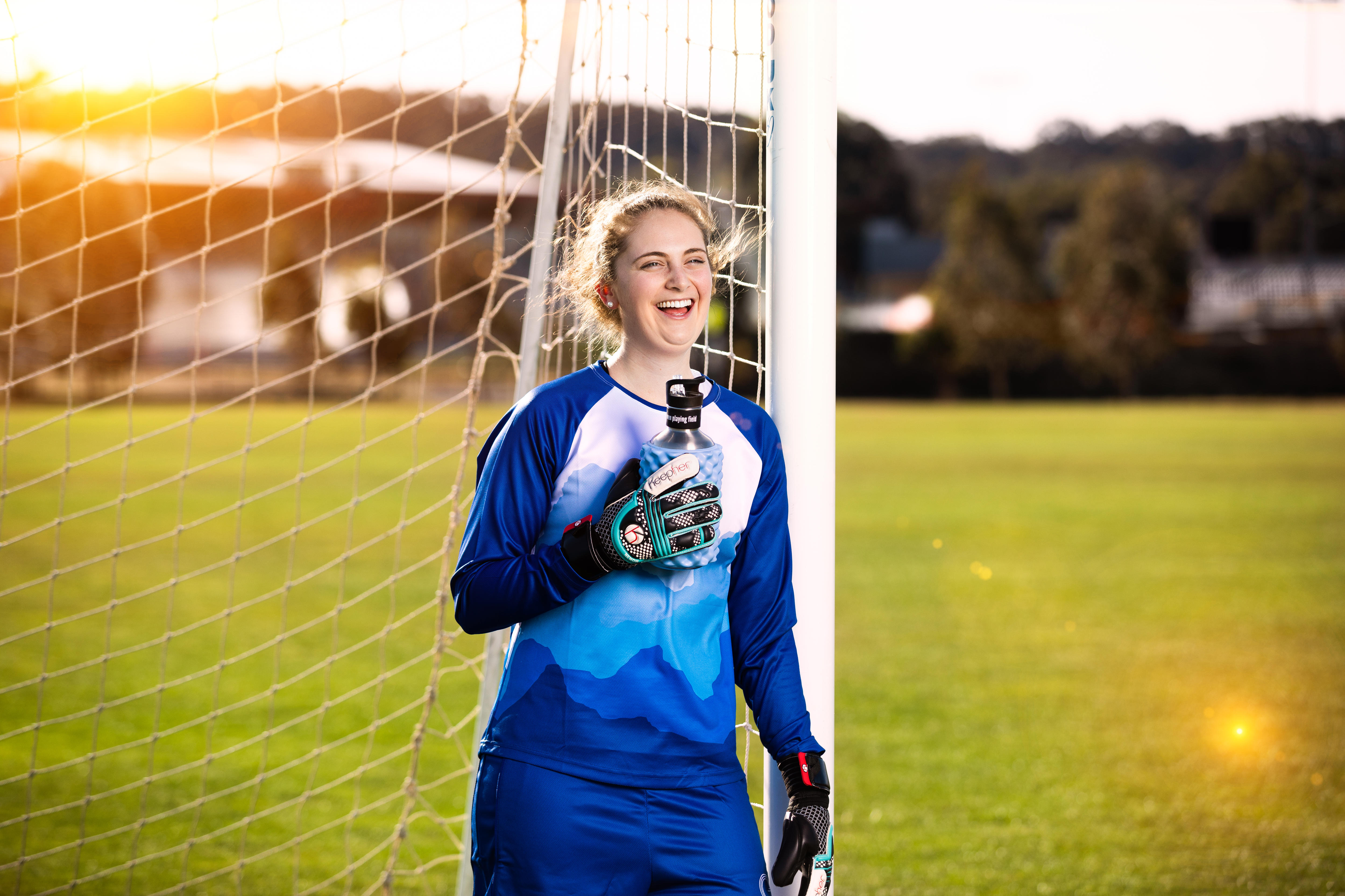 Female soccer player leaning against the right goal post smiling while  wearing her women's specific goalie gloves