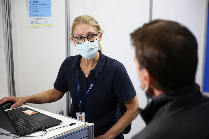 A vaccine nurse wearing a mask speaks to an out-of-focus Michael Rowland.