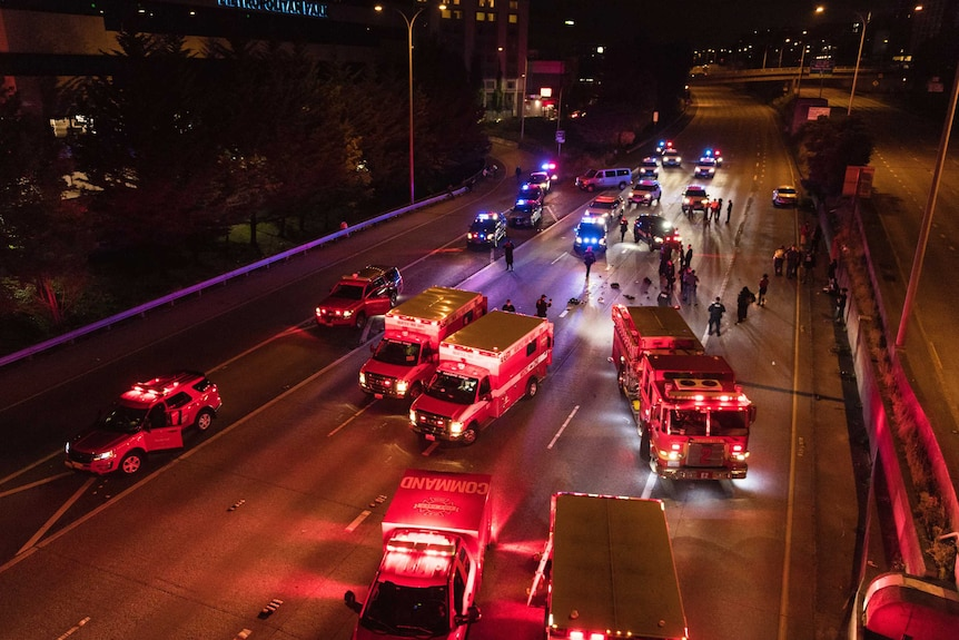 Emergency vehicles block an eight-lane highway at night, with flashing lights, with police on road.