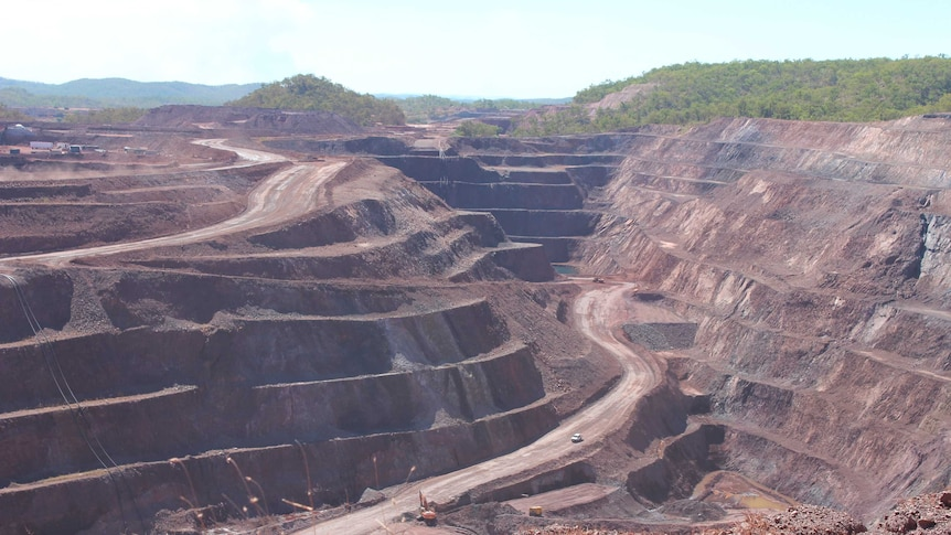 open cut mine pit showing the tiers of mining with a road going down to the bottom