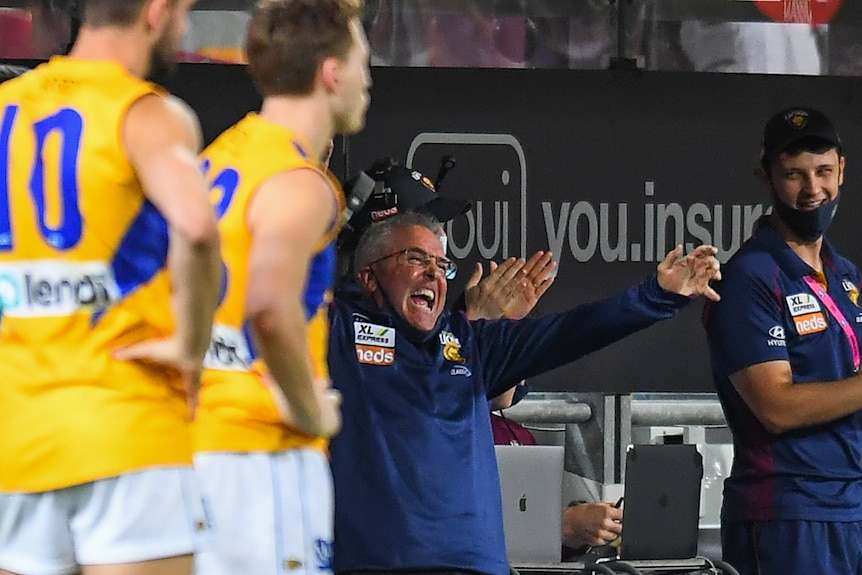 An AFL coach lets out a joyful roar at the end of the game as his team makes sure they finish fourth.