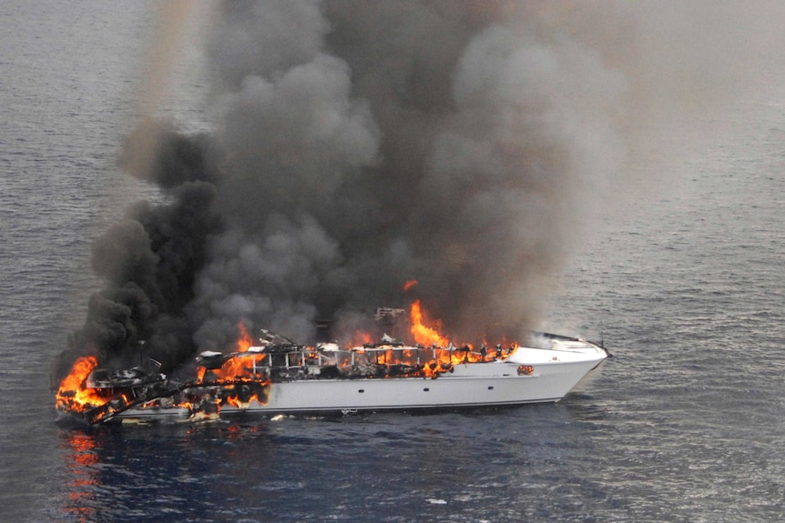 Flames pour from the luxury yacht, the Seafaris, after it caught on fire.