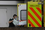 A paramedic pushes a patient into the back of an ambulance.