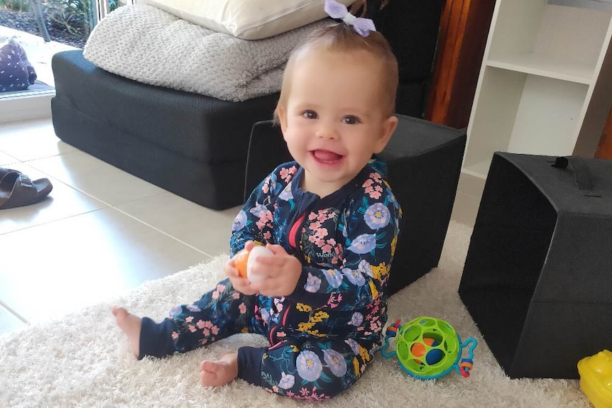 A baby wearing a hair tie smiles while playing with toys in a living room