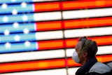A man in a face mask walks past an American flag